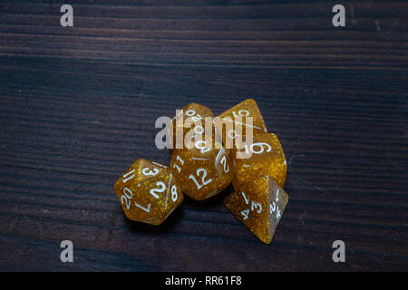 Set of glittery, gold polyhedral game dice grouped together on a wooden table - Stock Photo