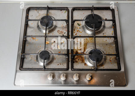 Dirty gas stove in the kitchen, top view. Gas stove with food remnants. - Stock Photo