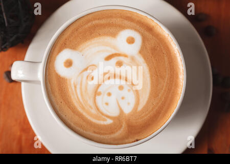 White Cup cappuccino coffee with a latte-art pattern in the form of a bear close-up on a wooden background. The concept of making coffee in a coffee s - Stock Photo