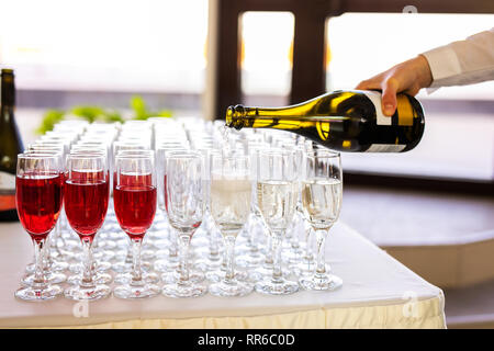 the waiter pours champagne in glasses on the street - wedding catering. - Stock Photo