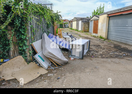 Large pile of rubbish, rotting after being fly tipped and left in an urban alleyway. Demonstrates anti-social behaviour. - Stock Photo