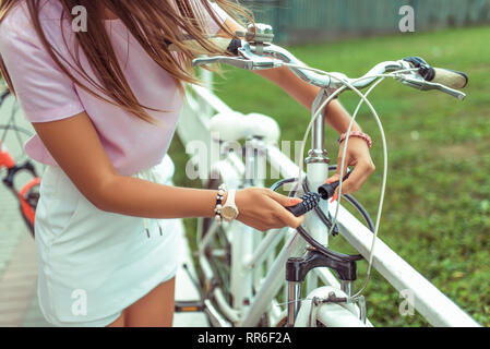 Girl in a pink T-shirt near the fence in the summer in the park. Locks, locks the cable with a code number. Protection against hijackings and scammers - Stock Photo