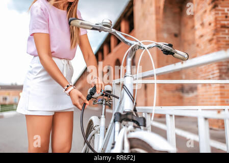 Woman in a pink t-shirt near fence parking in the summer in the park. Locks, locks the cable with a code number. Protection against hijackings and - Stock Photo