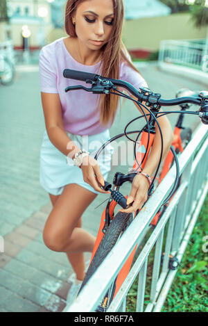 Beautiful girl in a pink t-shirt at fence parking in summer in the park. Locks, locks the cable with a code number. Protection against hijackings and - Stock Photo