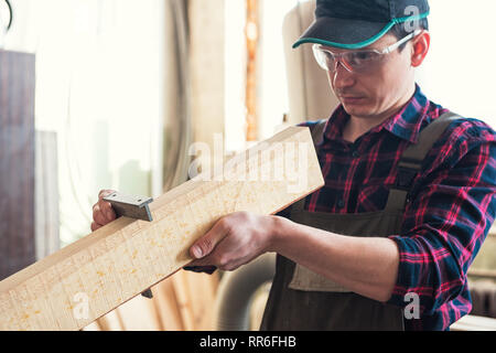 The worker makes measurements of a wooden board - Stock Photo