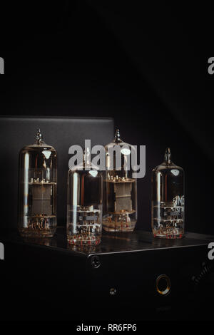 Headphone amplifier with four vacuum tubes / valves against a black background. Vertical / portrait aspect. - Stock Photo