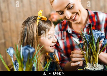 happy mother touching flowers in pot near cute daughter - Stock Photo
