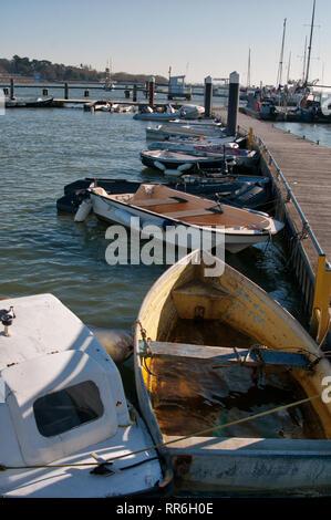 Dinghies tied up alongside a marina - Stock Photo