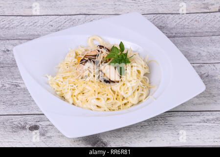 Italian pasta with mussels and cheese served basil leaves - Stock Photo