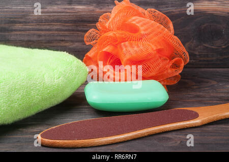 double-sided grater for feet with soap and shower sponge on a wooden background - Stock Photo