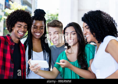 Group of laughing latin american and african young adults watching clip outdoor in the city - Stock Photo