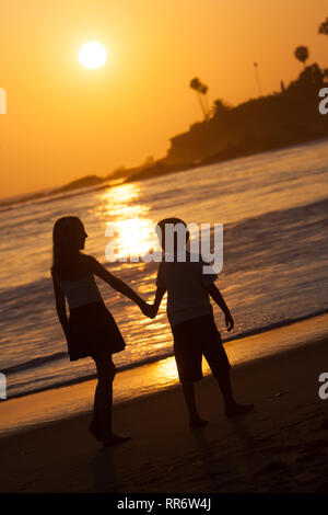 A silhouette of a siblings walking hand in hand along the shoreline of Laguna Beach, California. - Stock Photo