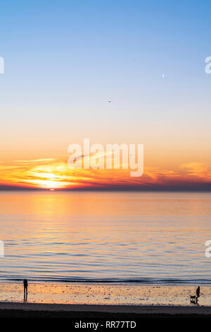 Sunrise, sunup, over the sea, English Channel, at Viking Bay Broadstairs. Thin band of cloud and orange sky on horizon with clear blue sky above. Single boat silhouette on sea. Seashore in lower frame. - Stock Photo
