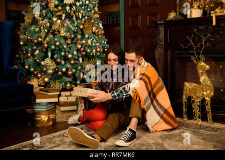 Young couple with gifts near Christmas tree - Stock Photo