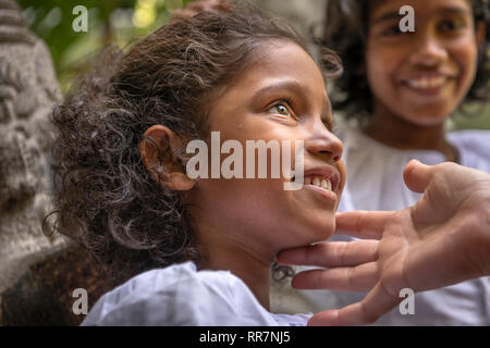 A little girl takes time out from Sunday School at the Gangaramaya Buddhist Temple in Colombo Sri Lanka. - Stock Photo