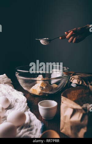 Woman's hand holding strainer with flour over glass bowl of diced butter next to ingredients for shortbread cookies. - Stock Photo