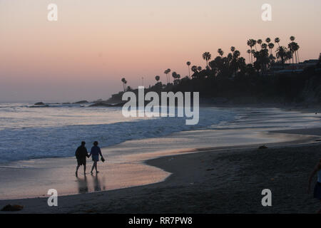 A silhouette of a couple walking hand in hand on long the shoreline of Laguna Beach, California. - Stock Photo