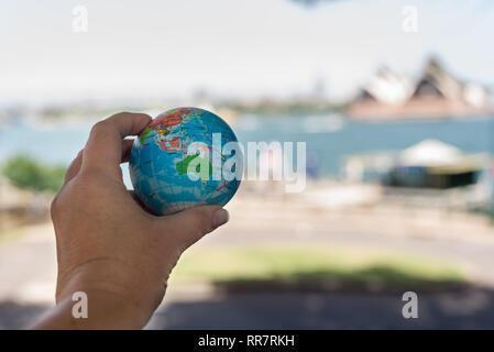 hand holding globe in front of famous Australian landmark, the Opera House - Stock Photo