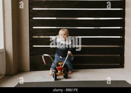 Precious Adorable Cute Little Blonde Baby Toddler Boy Kid Playing Outside on Wooden Toy Bicycle Scooter Mobile Smiling at the Camera and Having Fun