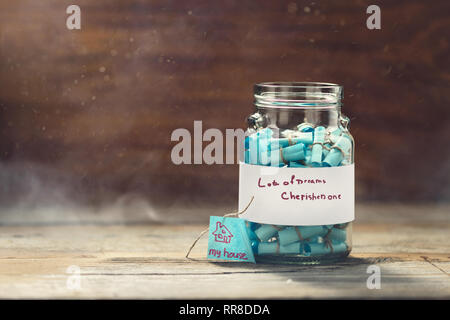Dreams jar. Dream house concept. Full glass jar of cherished wishes - Stock Photo