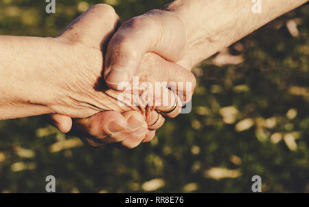Close-up image of shaking hands between elderly woman and man. Agreement Concept.