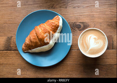 Cappuccino art and croissant on wooden background. - Stock Photo