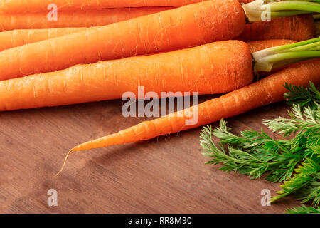 Fresh organic raw carrots on a dark rustic wooden background with a place for text - Stock Photo