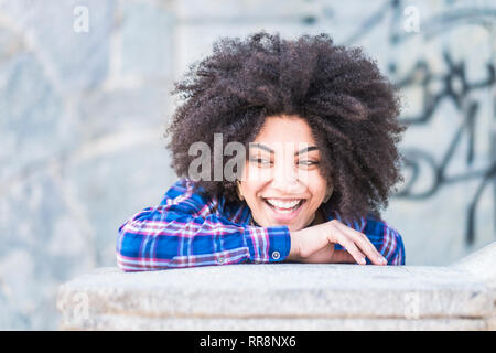 Young beautiful african hair young woman laughing and enojying in outdoor city place - cheerful hipster girl laugh and live with joy - female portrait - Stock Photo