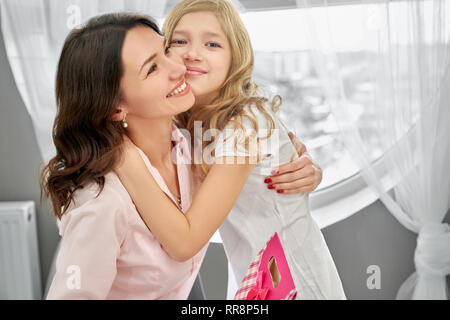 Pretty girl hugging gorgeous mother. Young, beautiful mommy and daughter smiling, happy together. Cheerful, joyful child and mom posing in light room  - Stock Photo