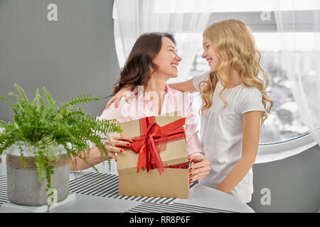 Cheerful daughter hugging happy mother. Beautiful brunette opening box with red bow on white table with houseplant. Mom looking with love and smile at - Stock Photo