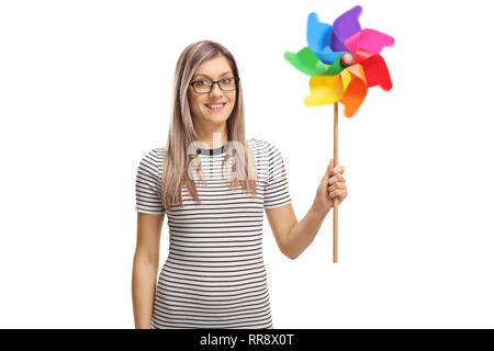 Smiling young woman with a spinning pinwheel in her hand isolated on white background - Stock Photo