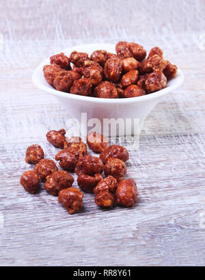 Sugared Hazelnuts in a white bowl on a wooden background. Hazelnuts in sugar glaze. Selective focus. - Stock Photo