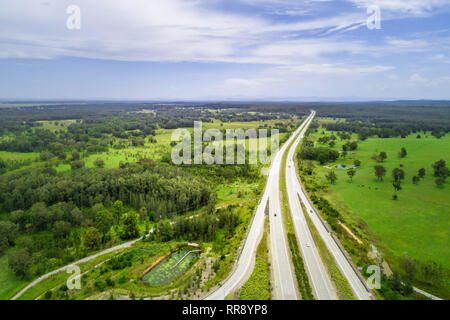Aerial view of highway passing through countryside on bright sunny day - Stock Photo