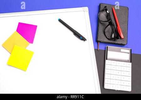 Modern workplace with office-board, pen and calculator isolated on blue black background - Stock Photo