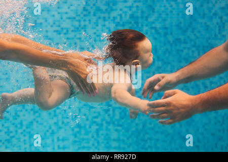 Father and mother teaching small child swimming underwater in the pool. Baby swimming - Stock Photo