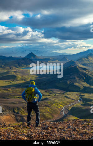 Hiker looking over the mountains and lake at Alftavatn, from Jokultungur on the Laugavegur hiking trail. Central Highlands, Sudhurland, Iceland. - Stock Photo