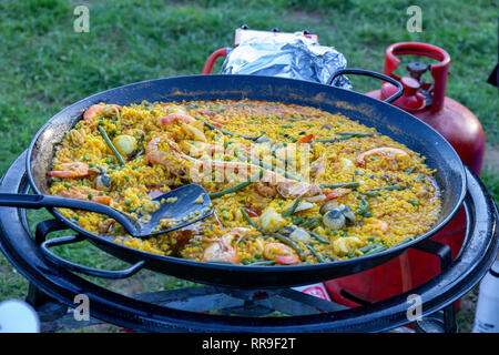 A large pan of seafood paella being served outdoors - Stock Photo