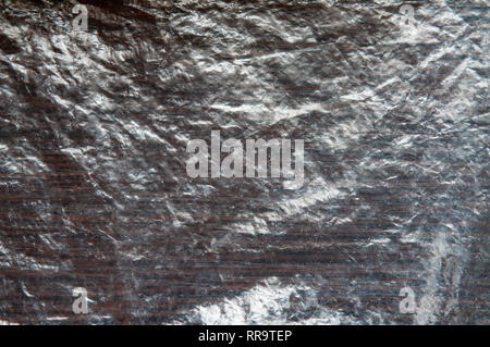 Dirty crumpled transparent cellophane on a dark wooden table. The texture can be used as a background - Stock Photo