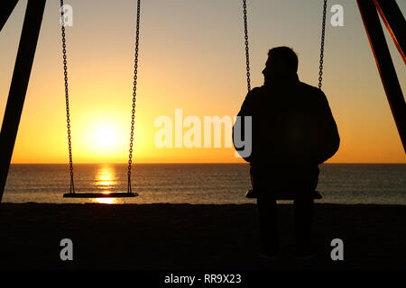 Back view backlighting silhouette of a man alone on a swing looking at empty seat at sunset on the beach in winter - Stock Photo
