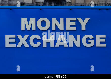 Close up view of blue light Money Exchange sign with spikes on top - Stock Photo