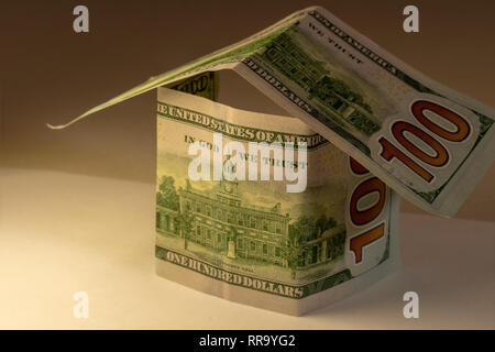 House shape made from hundred dollar bills. Real estate expenses building mortgage and property concept. - Stock Photo