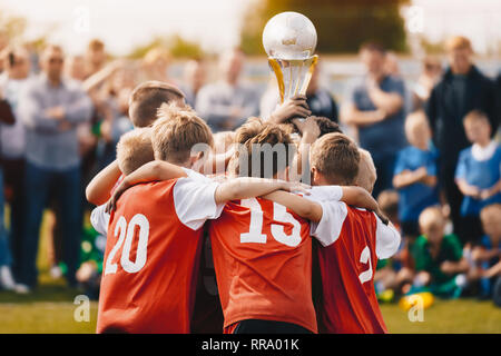 Young Athletes from School Sports Team Holding Winning Trophy. Kids Champion Sport Team. Boys Holding Prize Cup. Children Rising Winner Golden Cup. Bo - Stock Photo