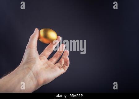 Man hand holding Golden egg on a black background - Stock Photo