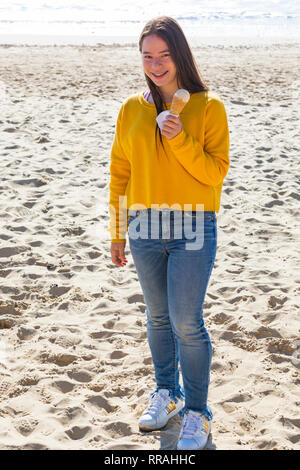 Bournemouth, Dorset, UK. 25th Feb, 2019. UK weather: another lovely warm sunny day at Bournemouth as visitors enjoy the sunshine at the beach on the hottest day of the year so far and hottest February day ever. Time for an ice cream - young woman holding ice cream. Credit: Carolyn Jenkins/Alamy Live News