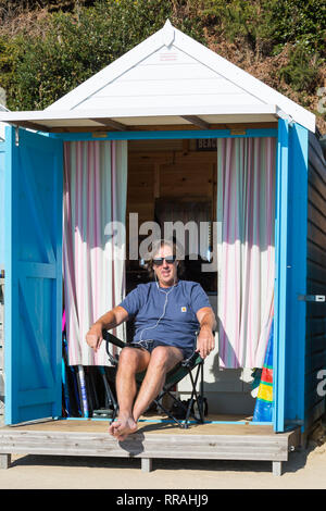 Bournemouth, Dorset, UK. 25th Feb, 2019. UK weather: another lovely warm sunny day at Bournemouth as visitors enjoy the sunshine at the beach on the hottest day of the year so far and hottest February day ever. Man relaxing in the sun at beach hut. Credit: Carolyn Jenkins/Alamy Live News