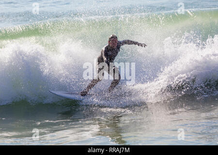 Bournemouth, Dorset, UK. 25th Feb, 2019. UK weather: big waves and plenty of surf create ideal surfing conditions for surfers at Bournemouth beach on a lovely warm sunny day expected to be the hottest day of the year and hottest February day ever. Surfer on surf board riding the waves.  Credit: Carolyn Jenkins/Alamy Live News