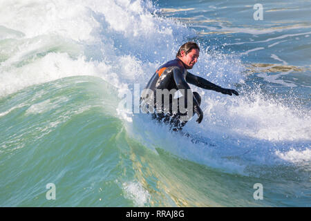 Bournemouth, Dorset, UK. 25th Feb, 2019. UK weather: big waves and plenty of surf create ideal surfing conditions for surfers at Bournemouth beach on a lovely warm sunny day expected to be the hottest day of the year and hottest February day ever. Surfer on surf board riding the wave. Credit: Carolyn Jenkins/Alamy Live News