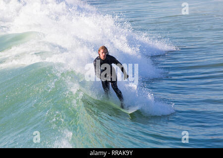 Bournemouth, Dorset, UK. 25th Feb, 2019. UK weather: big waves and plenty of surf create ideal surfing conditions for surfers at Bournemouth beach on a lovely warm sunny day expected to be the hottest day of the year and hottest February day ever. Surfer riding the wave. Credit: Carolyn Jenkins/Alamy Live News