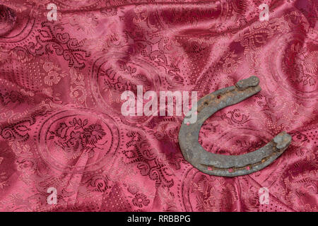 Horseshoe as a symbol of happiness on a silk red background - Stock Photo