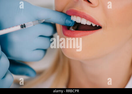 cropped view of dentist giving local anesthesia injection to woman - Stock Photo